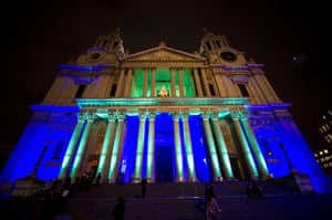 St Paul's Cathedral is lit up in blue and green to mark the Standard Chartered charity carol service in London, England.