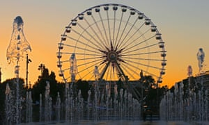 A ferris wheel is seen behind the water installation near a plaza decorated for Christmas, in Nice, southeastern France.