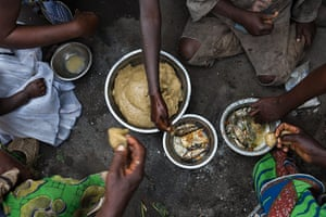 WWF Virunga Campaign: Local village family eating a meal of Fou Fou Kasava and fish
