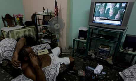 Cuban man watches Castro and Obama on TV