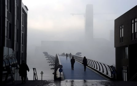 People walk through thick fog at the Millennium Bridge over the River Thames on December 11, 2013 in London, England. Fog today has caused travel disruption and delays with Heathrow and London City airports seeing more than 70 cancellations.