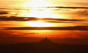 Glastonbury Tor is bathed in the golden light of the setting winter sun.