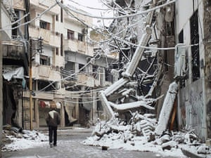 Winter in Syria: A man walks past debris from damaged buildings covered with snow in a besie