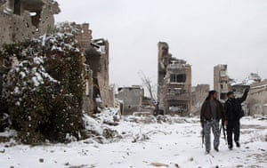 Winter in Syria: Free Syrian Army fighters walk past damaged buildings in the city of Aleppo