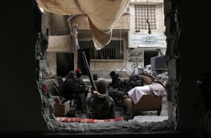 Winter in Syria: Free Syrian Army fighters warm themselves around a heater along a street in