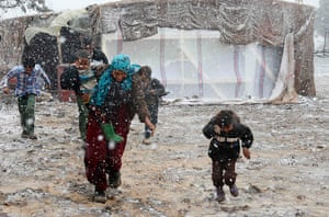 Winter in Syria: Syrian refugees run for cover from snow during a winter storm in the Bekaa