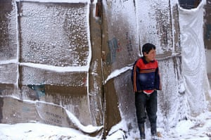 Winter in Syria: A Syrian refugee boy stands outside his tent in the Bekaa valley