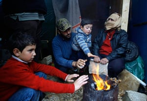Winter in Syria: Syrian refugees warm themselves around a bonfire near their tent as a heavy