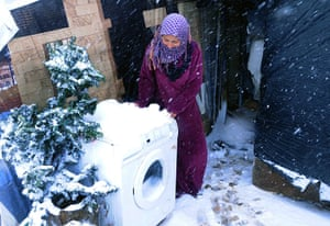 Winter in Syria: A Syrian refugee tries to move a washing machine outside her tent to protec