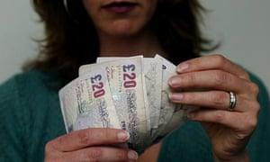 Woman counting bank notes, UK