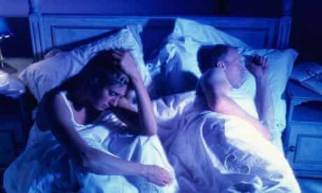 A sleepless woman in bed beside a sleeping man