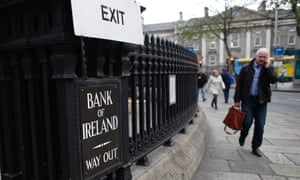 Shoppers pass the Bank of Ireland in Dublin on December 11, 2013.