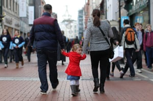 A family walks along the Grafton Street shopping area in Dublin .