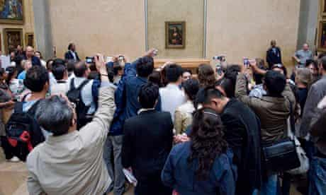Tourists photographing the Mona Lisa in the Louvre in Paris