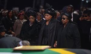 Winnie Madikizela-Mandela and Mandela's widow, Graca Machel, stand by his coffin.
