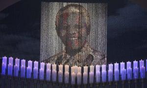 Candles are lit under a portrait of Neslon Mandela before the ceremony