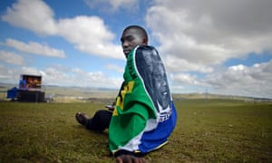 A young man watch the screen at the site where Mandela will be buried