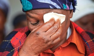 An elderly resident of Qunu wipes her tears as she watches the broadcast