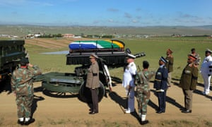 Nelson Mandela's coffin is brought to his funeral on a gun carriage by a military parade.