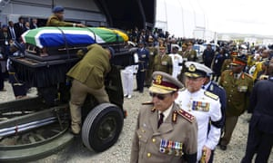 Mandela's coffin leaves the funeral tent before the burial, which is taking place on his family's property in Qunu.