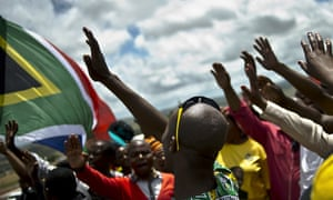 People wave goodbye to the late South African leader Nelson Mandela near his burial site.