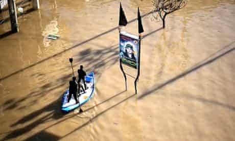 Two Palestinian men make their was along a flooded street in Gaza City