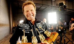 Troy Cassar-Daley holds his Golden Guitar awards