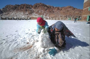 School children playing with snow at their school yard in Saint Catherine, south Sinai, Egypt.
