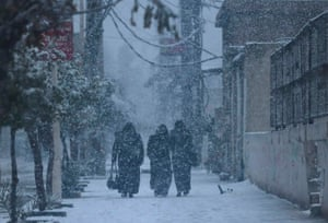 People walk along a street during snow fall in the Duma neighbourhood of Damascus.