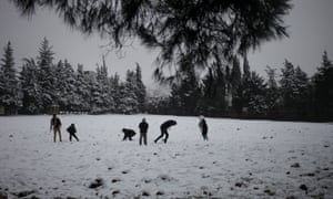 Jordanians play with the snow in an open field during a snowstorm in Amman, Jordan.