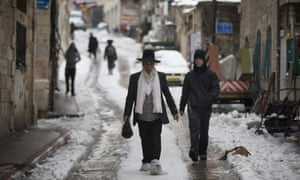 People walk in the snow in the Mea Shearim Ultra orthodox jewish neighborhood in Jerusalem, Israel. Heavy storms continued throughout Israel on Friday, causing traffic disruptions and power outages across the country.