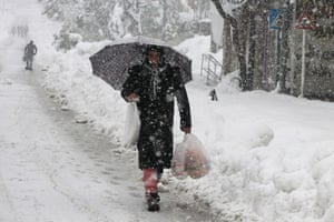 A Palestinian man holding shopping bags walks in a street of the West Bank town of Hebron as snow falls on December 14, 2013.