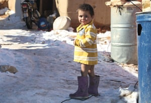 A Syrian child stands in the snow in the Arsal refugee camp in the Lebanese Bekaa valley on December 15, 2013.