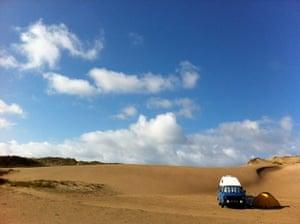 VW camper vans: blue VW camper van parked in the sand