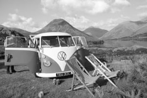 VW camper vans: VW camper and deck chairs in front of lake