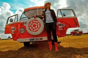 VW camper vans: woman in front of brightly coloured VW camper van