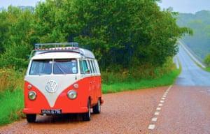 VW camper vans: red VW camper van parked in the rain