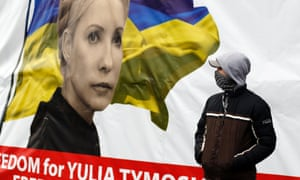A pro-European integration protestor stands next to a poster of jailed opposition leader Yulia Tymoshenko during a rally in Independence Square in Kiev. Photo: Reuters/Marko Djurica