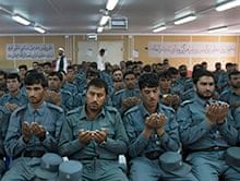 New Afghan national police officers pray during their graduation ceremony