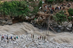 Extreme weather: Soldiers try to repair a temporary footbridge over River Alaknanda