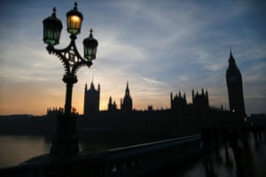 People cross Westminster Bridge with the Houses of Parliament behind at dusk in London, December 12, 2013..