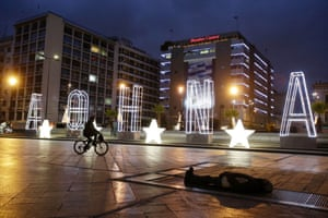 A man rides his bicycle next to a lit Christmas sign reading  ''Athens'' as a homeless man sleeps on a metro air vent above an underground station to warm up, at Omonia Square in central Athens, Monday, Dec. 16, 2013.