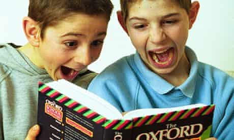 Schoolboys laughing while looking at a dictionary