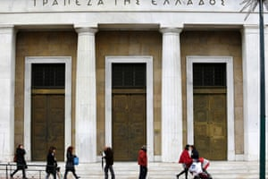 Pedestrians walk past the entrance of Bank of Greece in Athens today, Tuesday, Dec. 17, 2013.