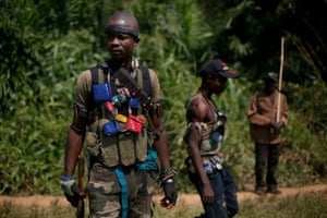 15 Dec: Anti-Balaka Christian militiamen walk through a forest clearing outside Bangui