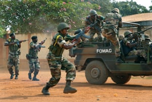 12 Dec: FOMAC troops, regional peacekeepers, fire their guns as they evacuate Muslim clerics from the St Jacques Church in Bangui.