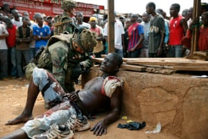 9 Dec: A French soldier speaks to suspected Christian militia member Sincere Banyodi, 32,  who lies wounded by machete blows in the Kokoro neighbourhood of Bangui. Vigilante crowds said they spotted him with grenades and turned him in to the French forces
