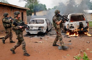 9 Dec: French troops patrol past two vehicles set on fire by Christian mobs in Bangui.