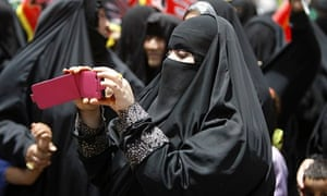 A Saudi woman films an Islamic ceremony on her phone