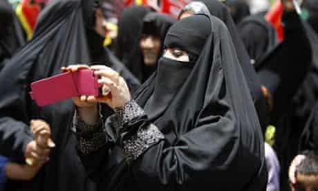 A Saudi woman films an Islamic ceremony on her phone